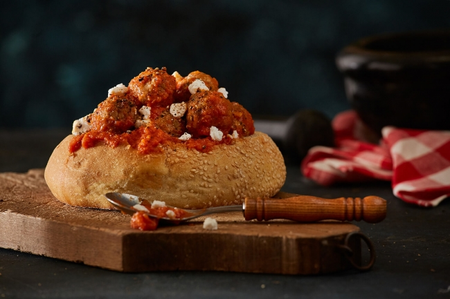 Meatballs with tomato sauce in a round loaf of bread