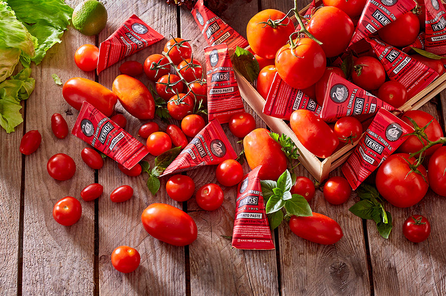 One-use paper-packaged KYKNOS tomato paste among tomatoes.